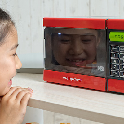 電子レンジのおもちゃで遊ぶ女の子